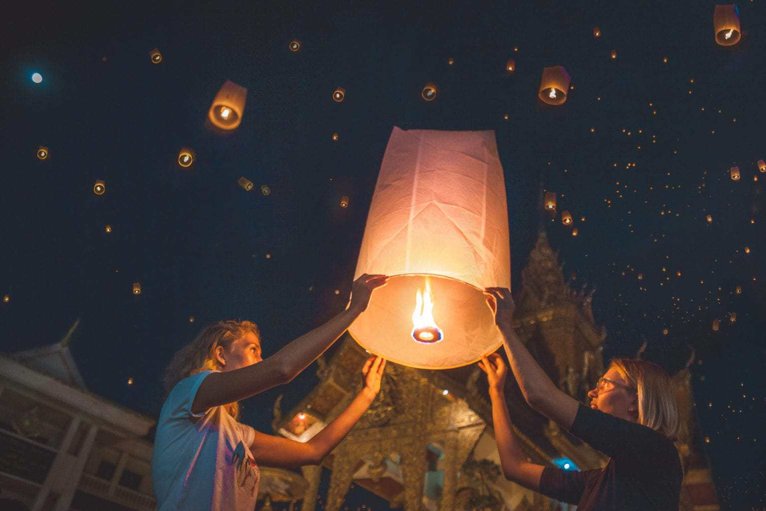 Holding a wishballoon/lantern during Chiang Mai's lantern festival Yi Peng, in front of a temple, with many lanterns lighting up the sky