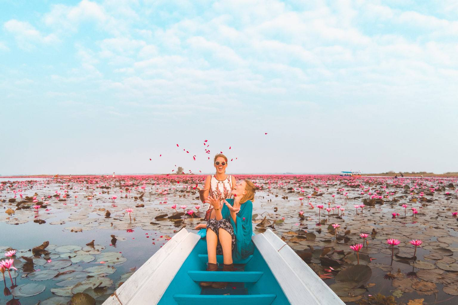 Once Upon A Journey Roxanne and Maartje a Lesbian travel couple on the red lotus lake in Thailand. Sitting on a boat surrounded by pink lotus sea, sprinkling rose leaves in the air celebrating love celebrating valentine's day 2018