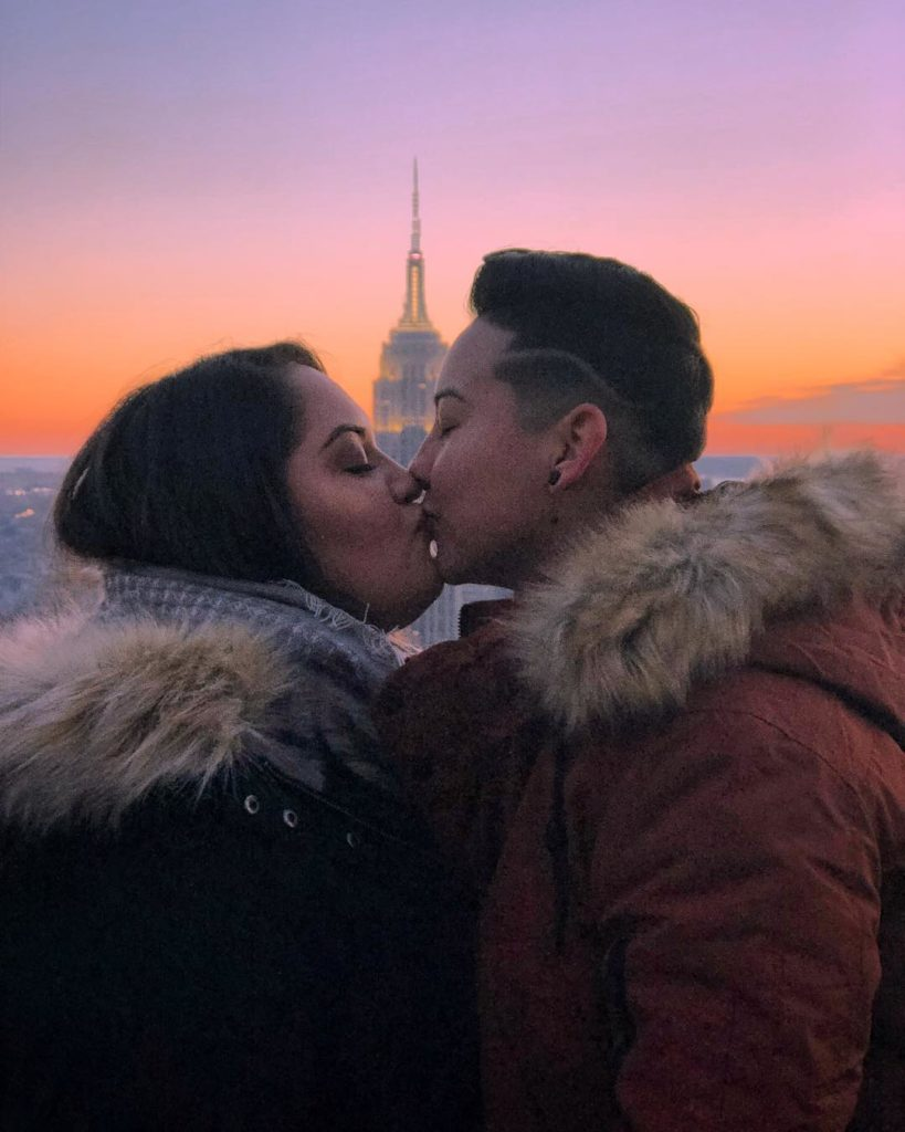 Lesbian instagram and youtube travel couple Jen and Abi kissing in front of the empire state building in New York City NYC, USA, during sunset or sunrise