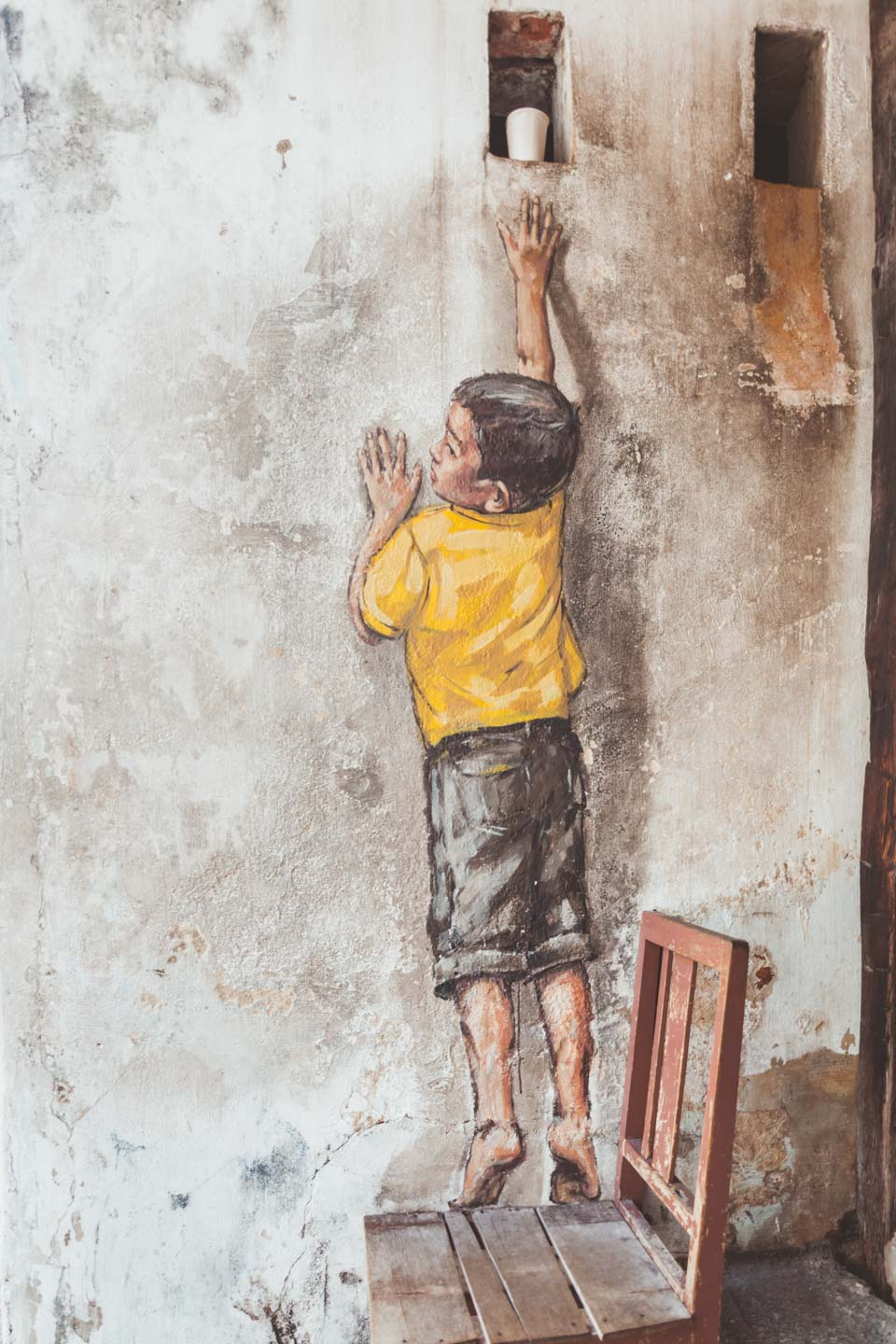 Ernest Zacharevic, Boy on Chair, Reaching Up, Penang Street Art, Malaysia