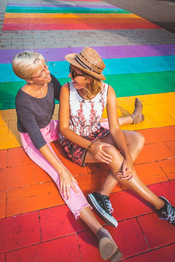 Gay couple sitting on rainbow crosswalk