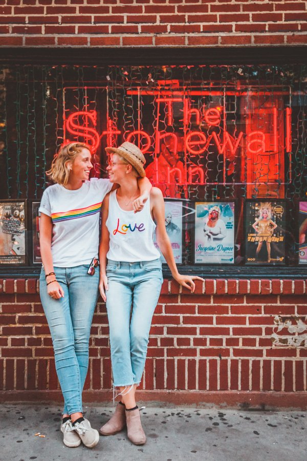 Lesbian couple standing in front of Stonewall Inn, where the Stonewall Riots happened in 1969