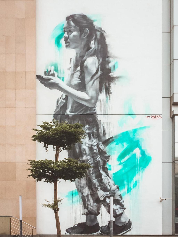 Looking up, mural of Caryn Koh by Emmanuel Jarus on shopping mall Penang